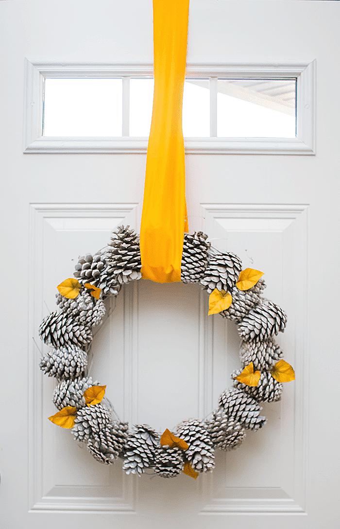 eine weiße tür aus holz und eine tür deko mit einem großen kranz mit einer gelben langen schleife und mit gelben kleinen blättern und vielen weißen bemalten tannenzapfen