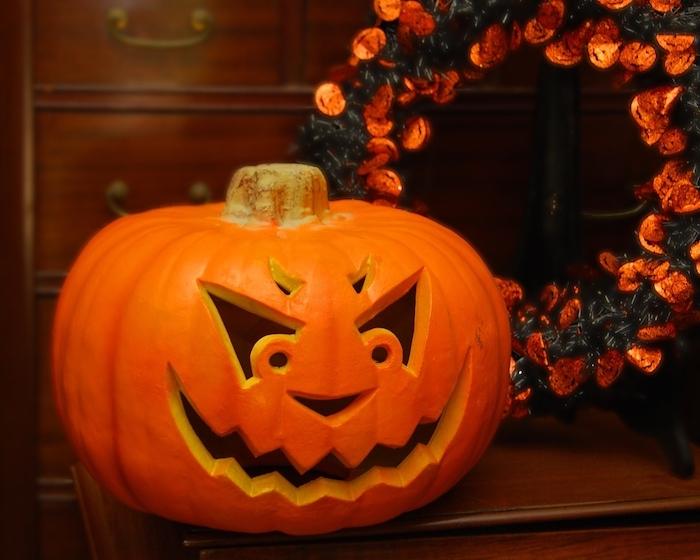 ein großer oranger halloween kürbis mit großen schwarzen augen und mit scharfen zähnen, ein kranz mit vielen kleinen orangen blumen und mit grünen blättern, gruselige kürbisgesichter schnitzen