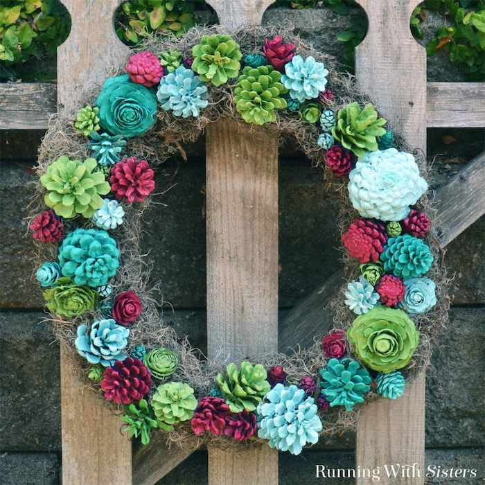 eine tannenzapfen deko selber basteln, tannenzapfen bemalen, ein kranz aus vielen rosen und mit kleinen grünen, roten und blauen blumen aus bemalten kleinen tannenzapfen