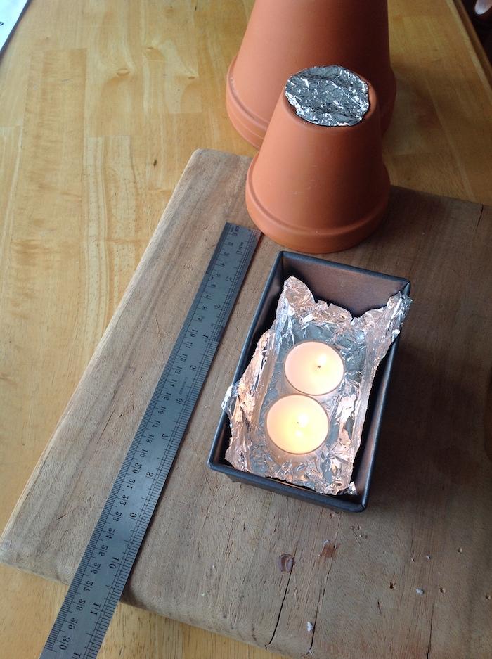 ein graues langes lineal und zwei kleine weiße teelichter, ein tisch aus holz und zwei braune blumentöpfe aus keramik, einen teelichtofen basteln