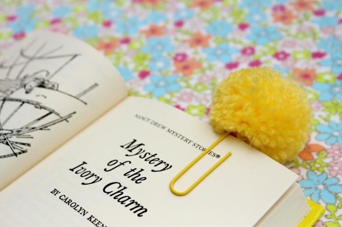 ein Lesezeichen selber basteln mit gelben Pompom und Klammer auf einem beliebten Buch