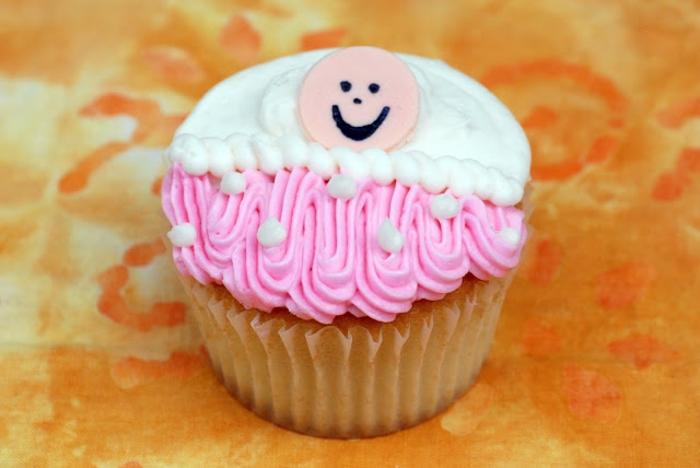 ein Cupcake mit ein lächendes Babygesicht, zwei Arten von Creme, Babyparty organisieren
