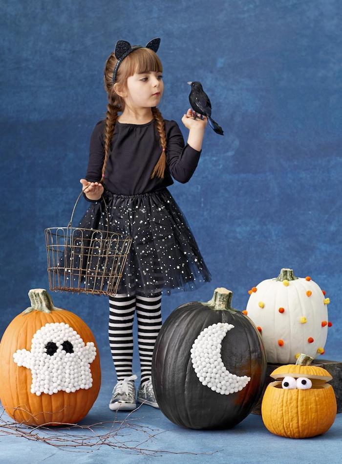 eine blaue wand und ein kleines mädchen mit schwarz-weißen socken und mit einem schwarzen kleid, ein schwarzer kleiner vogel, vier halloween deko kürbisse mit einem weißen geist und einem großen weißen halbmond, lustige kürbisgesichter