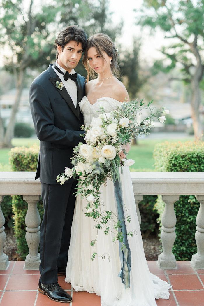 ein wasserfall brautstrauß weiß mit vielen weißen rosen und mit grünen blättern, ein mann und eine junge braut mit einem vintage brautkleid im garten