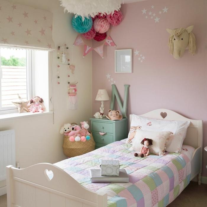 ein kleines Kinderzimmer, altrosa Farbe mit Einhorn Skulptur, ein blauer Nachttisch, Girlanden