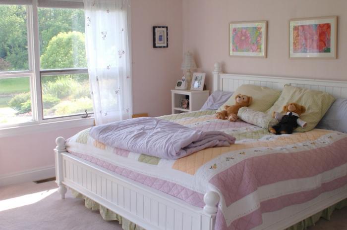 altrosa Farbe, großes Bett, bunte Bettwäsche, Gardinen mit Blumenmuster, zwei Bilder von Blumen