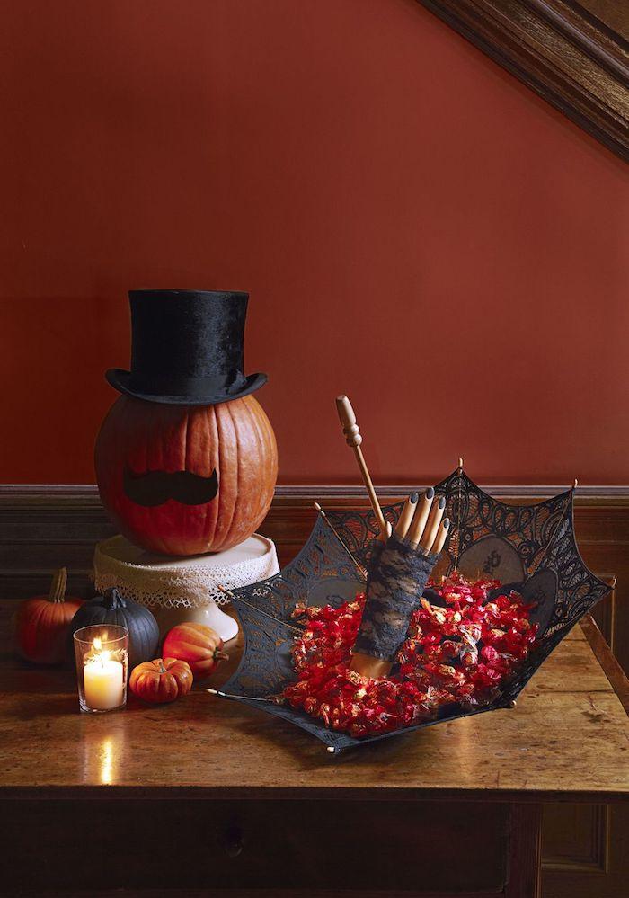 ein schwarzer regenschirm und ein kleiner oranger halloween kürbis mit einem lustigen kürbisgesicht mit schnurrbart aus einem schwarzen papier und mit einem schwarzen hut, kleine kürbisse halloween und eine weiße kerze und ein tisch aus holz