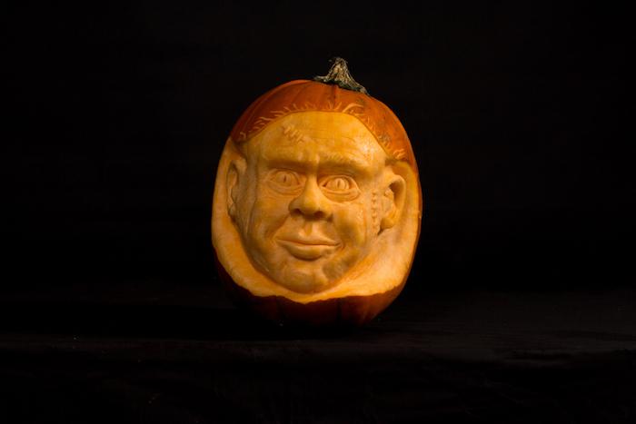 halloween dekoration mit einem großen orangen kürbis halloween mit einem gelben kürbisgesicht mit großen gelben augen und ohren und lippen, gruselige kürbisgesichter vorlagen