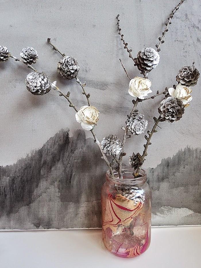 ein bild mit einem schwarzen berg und ein glas mit einer tannenzapfen deko mit ästen mit kleinen weißen rosen und mit bemalten metallic tannenzapfen