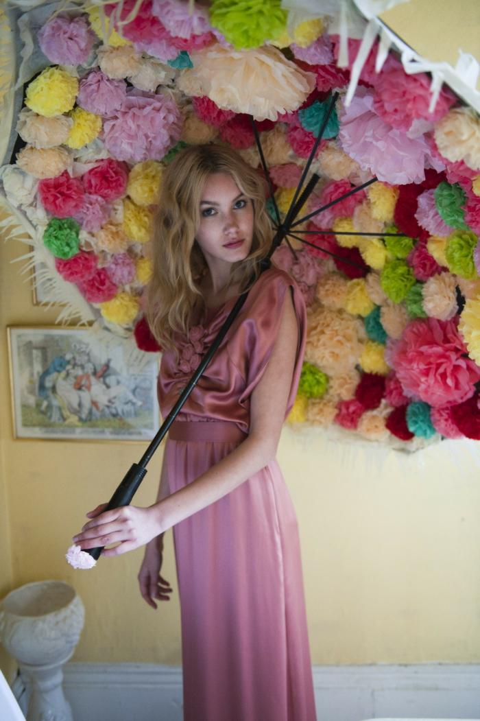 ein Mädchen mit rosa Kleid, ein Regenschirm mit Pompons geschmückt, Pompon machen