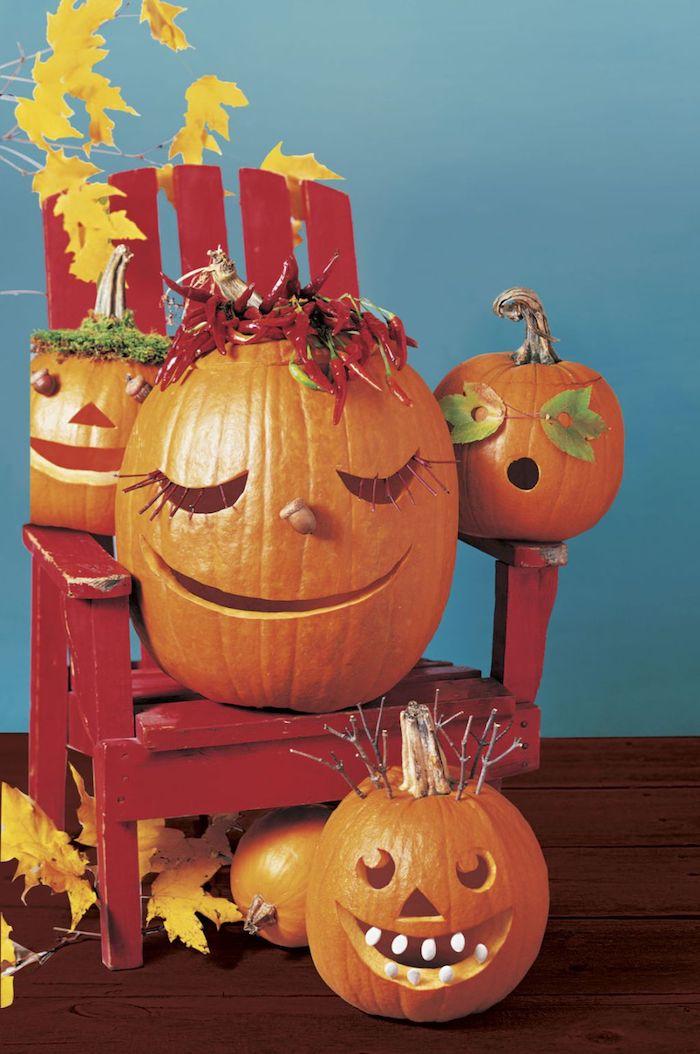 eine blaue wand und ein kleiner roter stuhl aus holz mit kleinen orangen kürbissen mit halloween kürbisgesichtern und vielen gelben blättern, lustige kürbisgesichter schnitzen