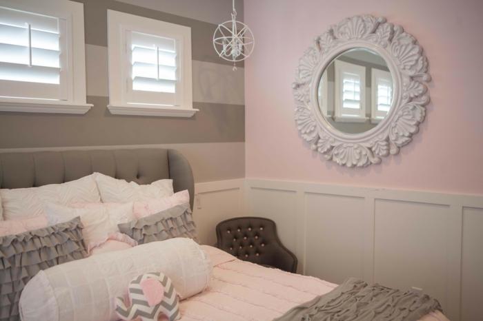 schlafzimmer in altrosa Farbe, viele Kissen symmetrisch gelegt, ein kleiner Stuhl in der Ecke