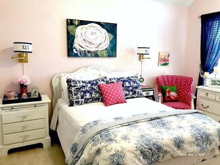 ein weißes bett mit viooletten und blauen kissen, schlaftzimmer einrichten, ein blauer vorhang und ein violettes sofa mit einem kissen mit einer pinken flamingo, ein bild mit einer rose