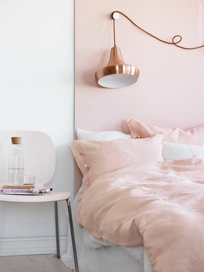 altrosa Farbe über das Bett, altrosa Bettwäsche, eine goldene Leselampe, Laminat Boden