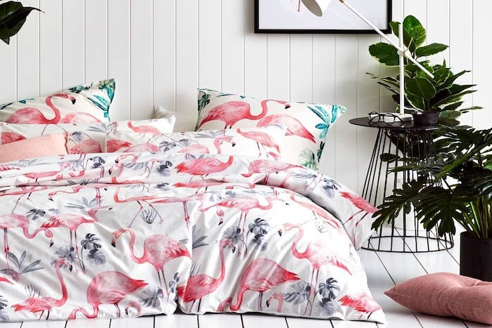 schlafzimmer einrichtung, eine weiße wand aus holz und ein bett mit einer weißen decke mit vielen kleinen pinken flamingos und mit zwei kissen mit flamingos