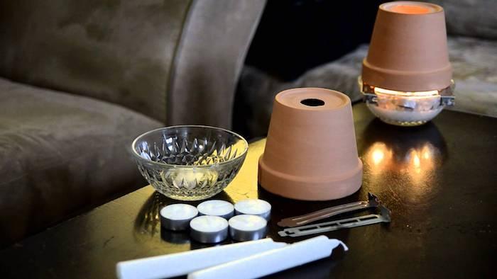 ein graues sofa und ein schwarzer tisch mit fünf kleinen weißen teelichtern und blumentöpfen aus keramik, teelichtofen materialliste