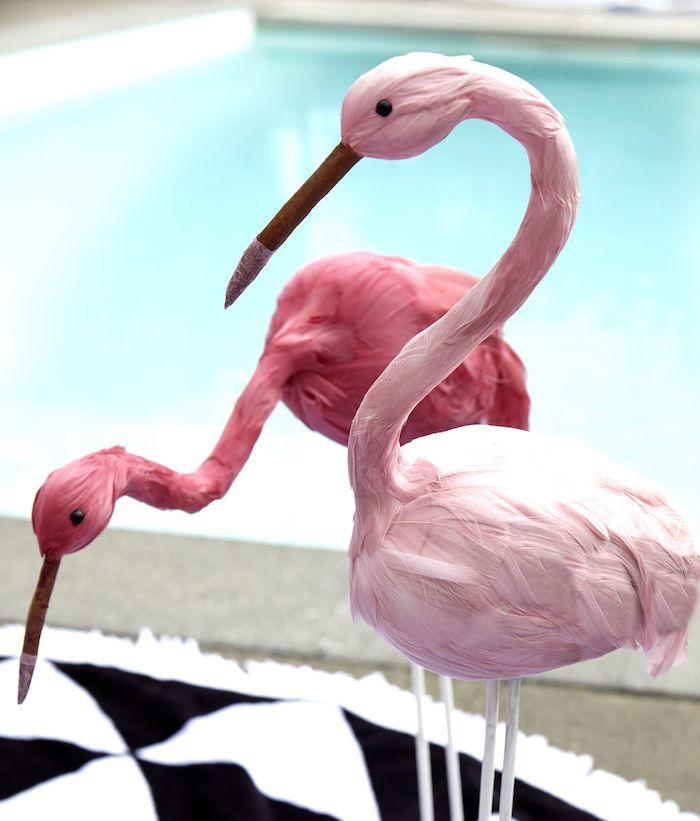 ein kleiner schwarz-weißer teppich und ein blaues schwimmpoool und zwei große pinke deko flamingos mit pinken federn, pink flamingo