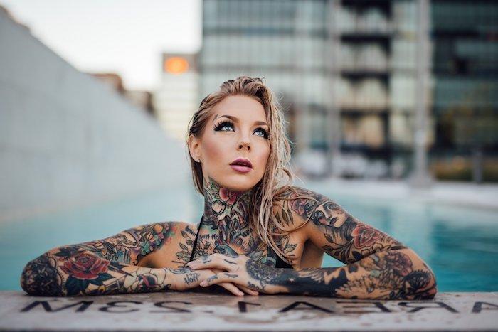 eine junge frau mit vielen tattoos moit roten rosen und mit kleinen grünen blättern und ein schwimmpool, tattoos frauen ideen