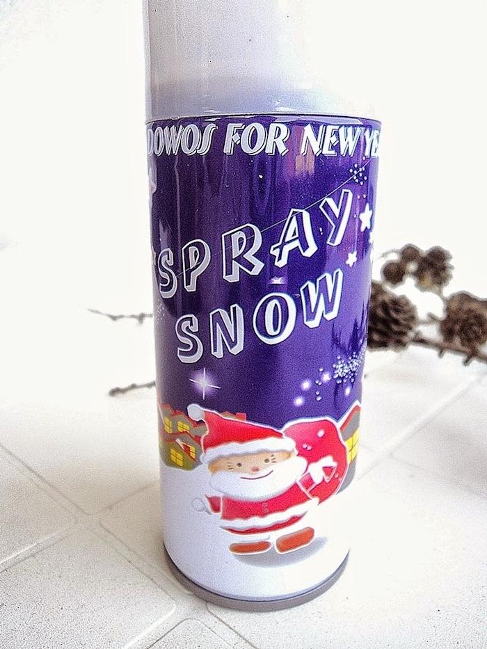 ein boden aus weißen fliesen und ein spray snow mit einem bild mit einem weihnachtsmann und kleinen häusern, äste mit braunen tannenzapfen