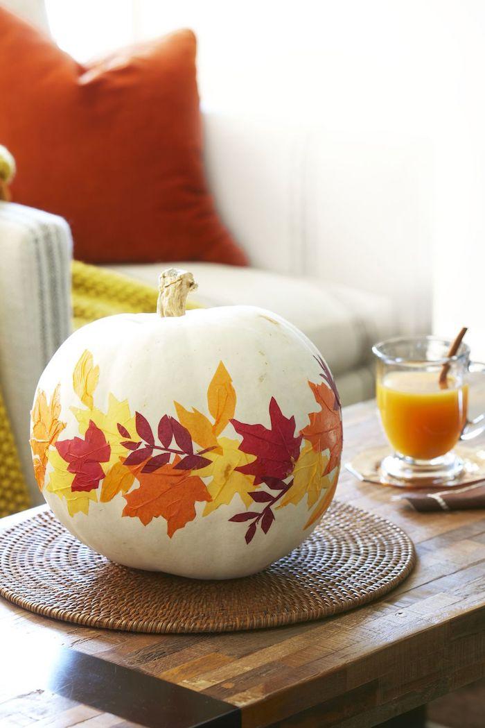 ein tisch aus holz, ein glas mit einem orangen saft, einen weißen halloween kürbis malen mit gelben, roten und orangen blättern, halloween dekoration selber machen