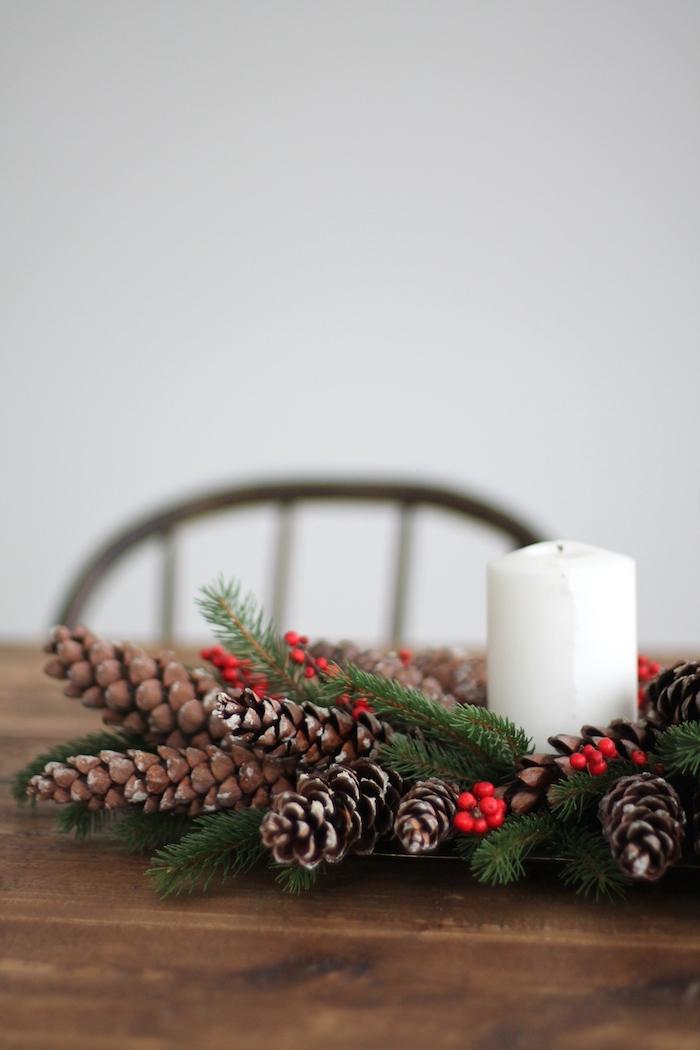 ein brauner tisch aus holz und ein stuhl und eine weiße wand, einen adventskranz selber bauen, ein kranz mit einer weißen kerze und mit kleinen braunen tannenzapfen und ästen mit ilex mit roten früchten