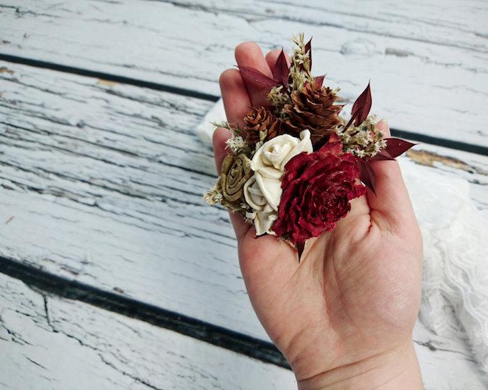 ein weißer tisch aus holz und eine hand mit einer kleinen tannenzapfen deko mit einer kleinen weißen rose, einer roten rose und einem tannenzapfen und roten blättern