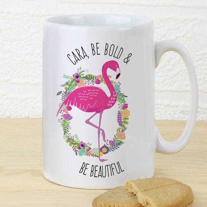 eine weiße tasse mit einer pinken flamingo und mit einem großen kranz mit vielen violetten, orangen und pinken blumen und grünen blättern und ein boden aus holz und eine weiße wand