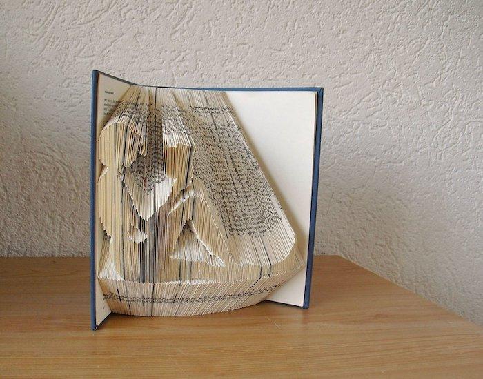 eine frau liest ein buch, eine figur aus vielen weißen gefalteten seiten eines kleinen buchs mit einem blauen bucheinband, eine weiße wand und ein tisch aus holz