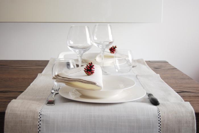 eine tisch deko mit einer weißen decke und weißen tellern und weingläser und zwei kleinen roten bemalten tannenzapfen, eine tannenzapfen deko