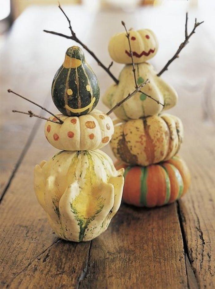 lustige kürbisgesichter malen, ein tisch aus holz und kleine wesen aus kleinen orangen, weißen und grünen kürbissen und ästen