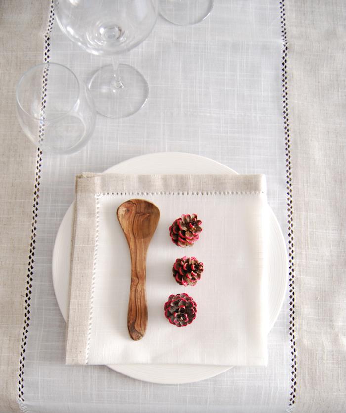 eine tisch deko mit weißen tellern und einer weißen decke und mit einem kleinen braunen löffel aus hilz und drei kleinen violetten bemalten tannenzapfen, eine tannenzapfen deko