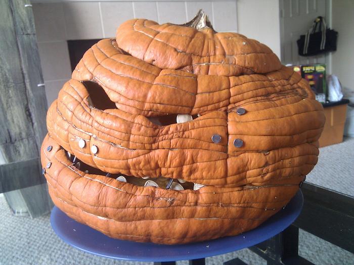 halloween deko selbst basteln, ein tisch und ein blauer teller mkt einem großen orangen kürbis halloween, gruselige kürbisgesichter, ein kürbis gesicht