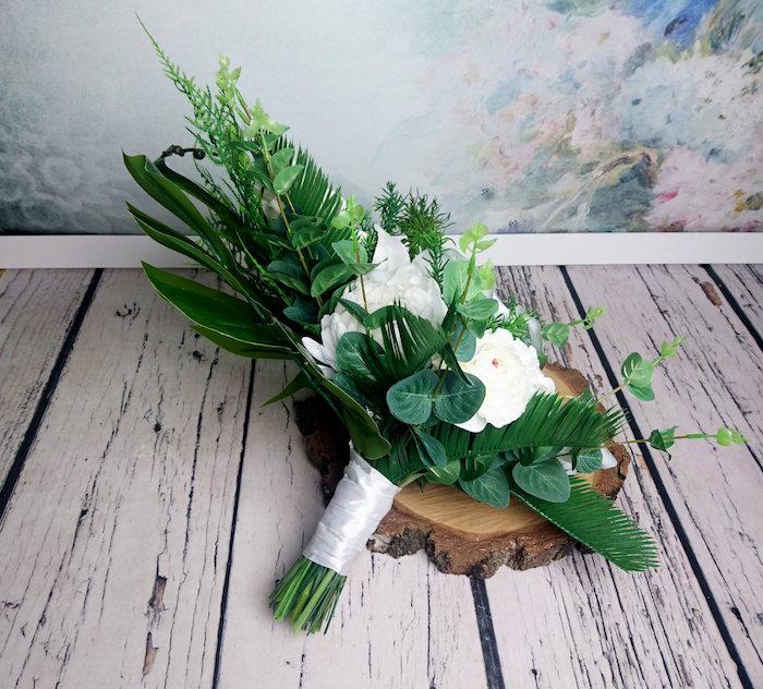ein weißer boden aus holz und ein kleiner brautstrauß mit vielen grünen blätrtern und weißen rosen und blumen und grünen blättern, einen brautstrauß gestalten