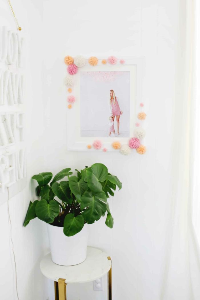 ein Rahmen in rosa und orange Farbe, eine grüne Pflanze, Pompon machen