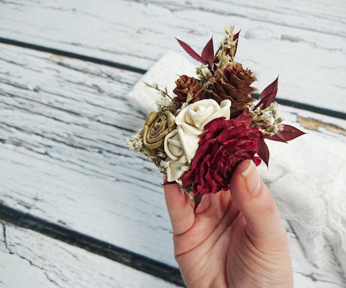 ein weißer tisch aus holz, basteln mit tannenzapfen, eine hand und eine kleine tannenzapfen deko mit einem braunen tannenzapfen und mit weißen, roten und goldenen rosen