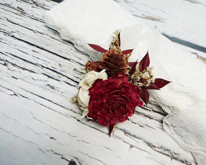 eine tischdeko mit kleinen tannenzapfen und rotem weißen und goldenen rosen und roten kleinen blättern, ein weißer tisch aus holz und eine weiße decke
