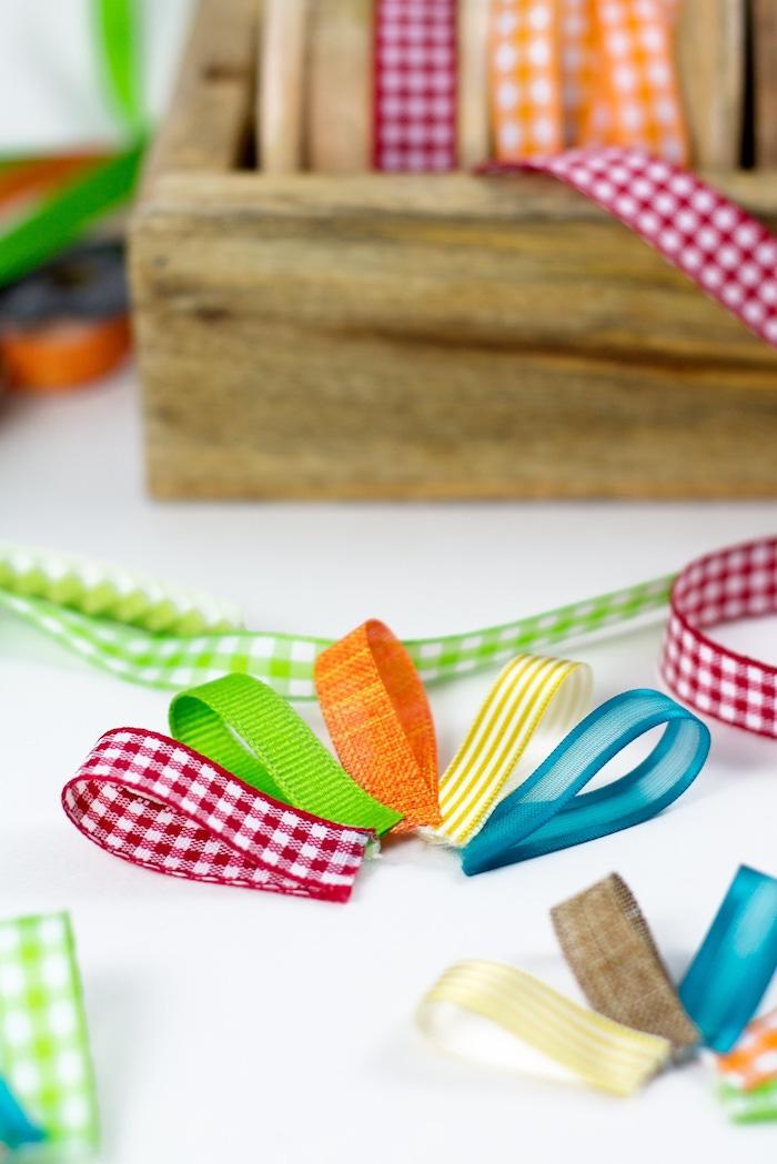 eine deko mit vielen kleinen orangen, blauen, grünen und roten gefalteten schleifen, eine frühlingsdeko selber basteln anleitung