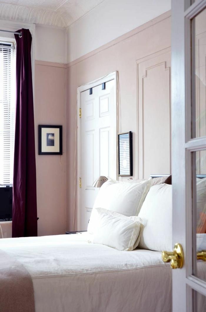 Altrosa Farbe in dem Schlafzimmer, weiße Kissen, lila Vorhänge, zwei Bilder, Rollos am Fenster