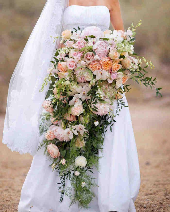 ein langer großer brautstrauß wasserfalll vintage mit vielen pinken und orangen rosen und grünen blättern, eine braut mit einem weißen brautkleid, ein wasserfall brautstrauß rosa