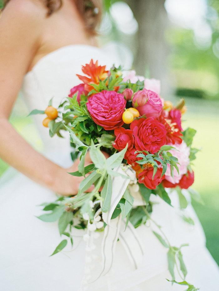 ein wasserfall brautstrauß rosa mit vielen violetten und roten rosen und grünen blättern, eine braut mit einem weißen brautkleid, einen brautstrauß gestalten