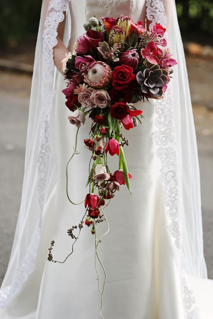 einen brautstrauß kaufen, eine braut mit einem weißen langen brautkleid und mit einem langen großen wasserfall brautstrauß mit vielen roten und pinken rosen und mit grünen blättern