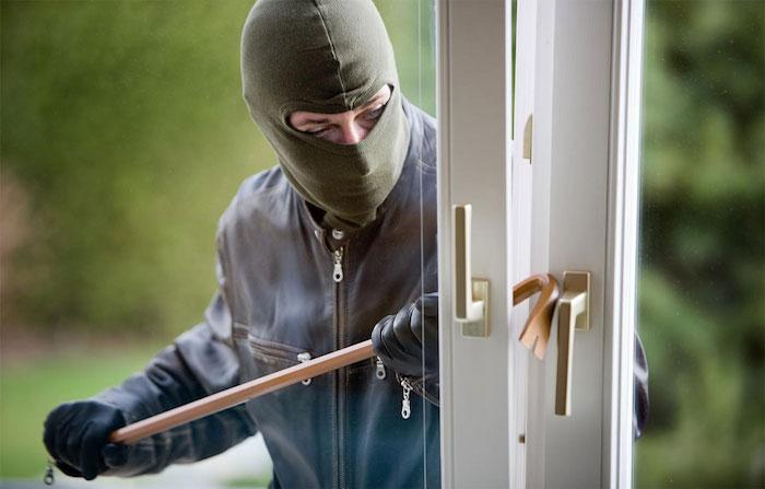 ein einbrecher mit einer grünen maske und ein weißes fenster, einbruchschutz