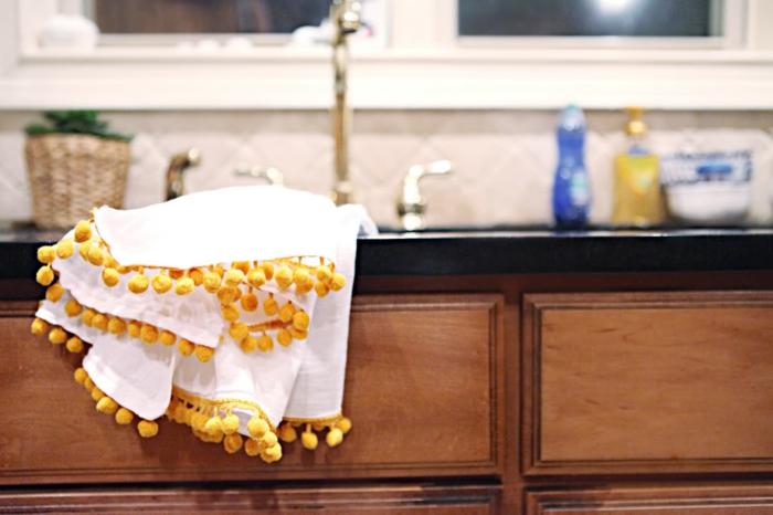 ein weißes Tuch mit gelben Pompons als Deko, Pompon machen aus gelbem Garn