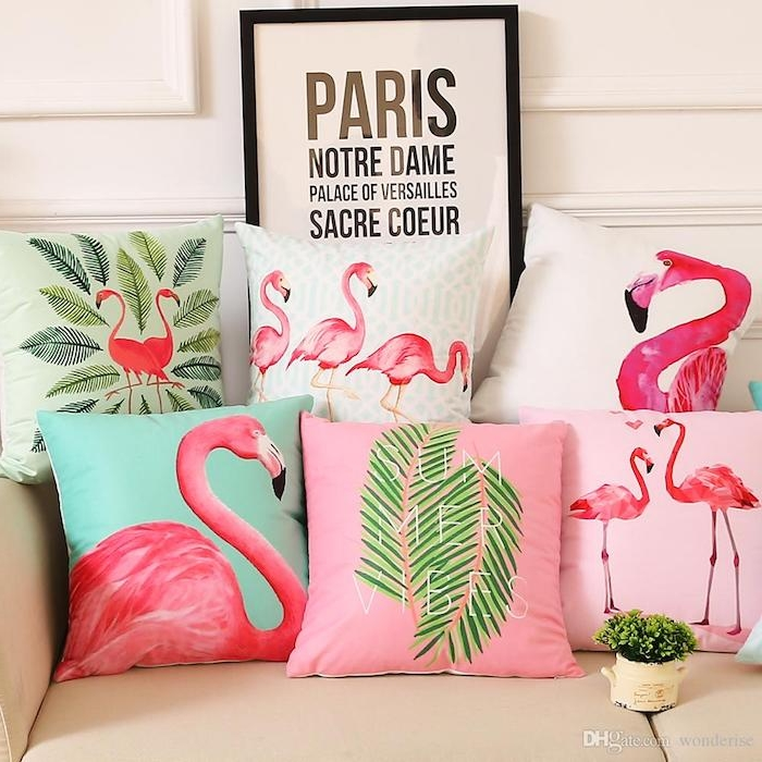 ein sofa mit vielen blauen, pinken, grünen und weißen kissen mit kleinen und großen pinken flamingos und mit grünen blättern, flamingo bilder