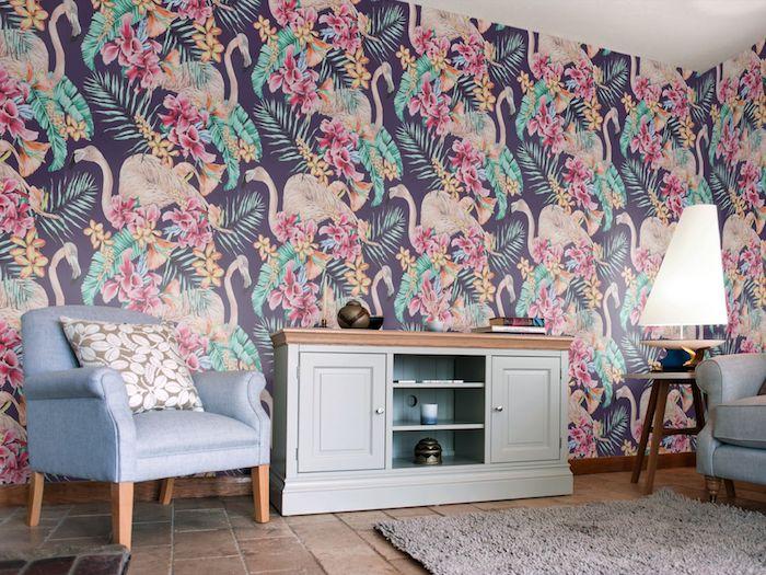 ein wohnzimmer dekorieren, eine große bunte flamingo tapete mkit vielen pinken fliegenden flamingos und mit grünen blättern und palmen und vielen pinken und violetten blumen, ein kleines blaues sofa mit einem weißen kisssen mit kleinen weißen blumen u8nd eine weiße lampe, flamingo deko