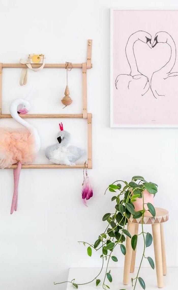 ein bild mit einem schwan und eine weiße wand, ein stuhl aus holz und ein flamingo spielzeug, eine pflanze mit grünen blättern
