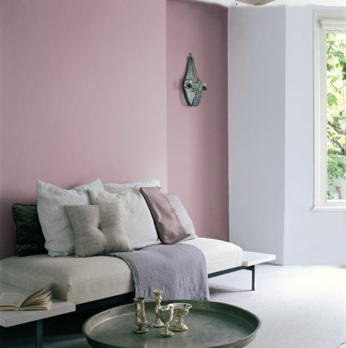 altrosa Wandfarbe, kleine graue Kissen, eine blaue Decke, ein gerundeter Tisch