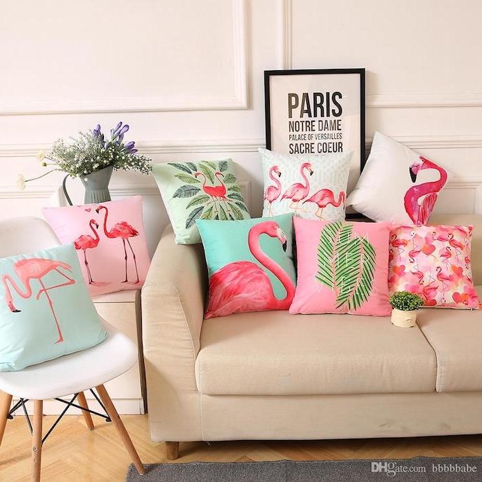 ein weißer stuhl und eine graue vase mit vielen weißen und violetten blumen mit grünen blättern, viele kleine kissen mit kleinen und groén pinken flamingos und grünen palmen