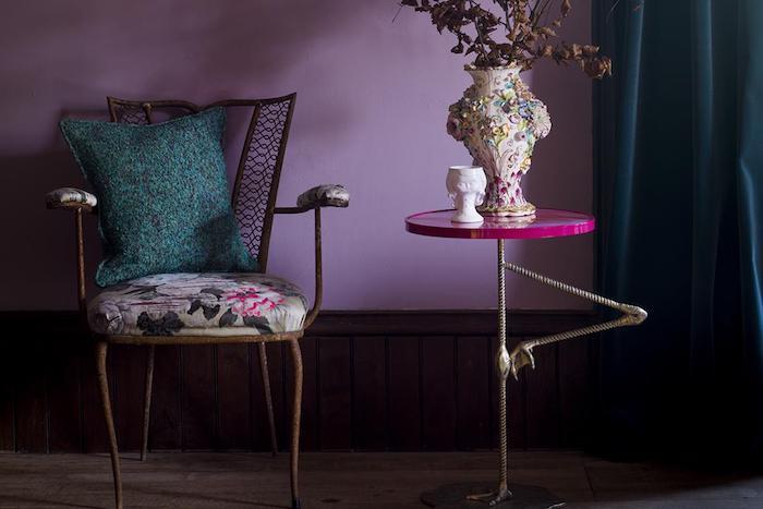 ein stuhl mit einem grünen kissen und ein kleiner violetter flamingo tisch mit einer bunten vase mit pflanzen und eine vilette wand