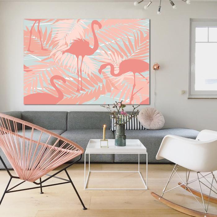 ein graues sofa und ein bild mit vielen pinken flamingos mit pinken federn und mit pinken und blauen palmen, ein kleiner tisch mit einer kerze und einer vase, boden aus holz und zwei stühle